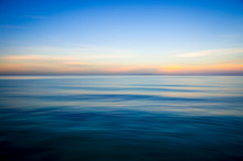 Abstract View Of The Glassy Smooth Surface Waves Of A Calm Sea During The Magic Hour Of Sunrise