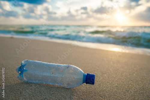 Photographie  Used plastic water bottle washed up on the shore of a tropical beach, highlighti