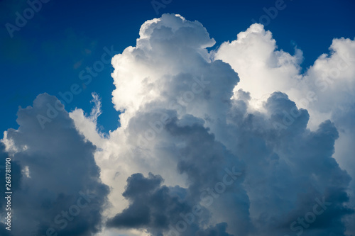 Fotografering  Abstract view of billowing thunderstorm clouds building against bright blue summ