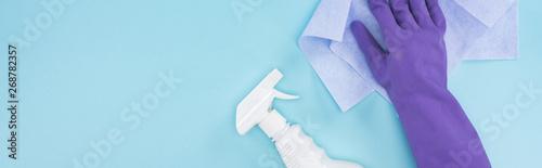 Fényképezés  panoramic shot of cleaner in purple rubber glove holding rag near spray bottle w
