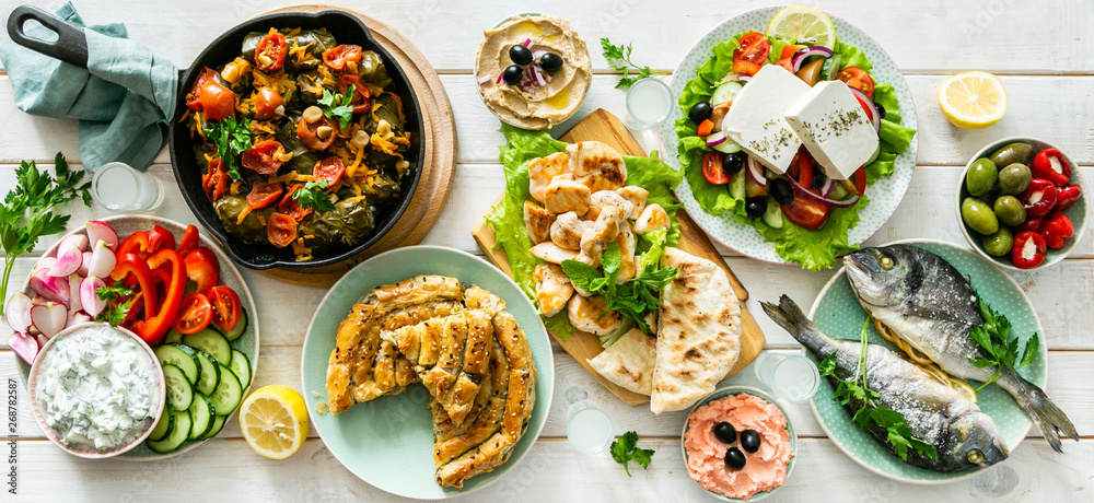 Fototapety, obrazy: Selection of traditional greek food - salad, meze, pie, fish, tzatziki, dolma on wood background, top view
