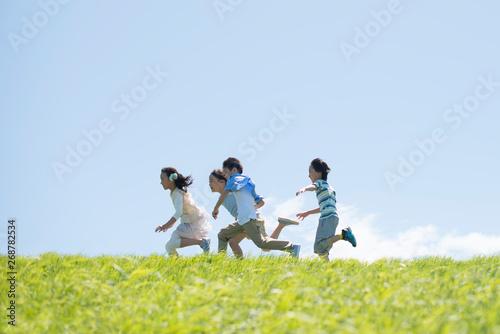 Obraz 草原を走る小学生 - fototapety do salonu