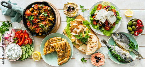 Aluminium Prints Food Selection of traditional greek food - salad, meze, pie, fish, tzatziki, dolma on wood background, top view