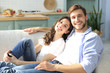 canvas print picture - Portrait of cute young couple sitting in sofa.