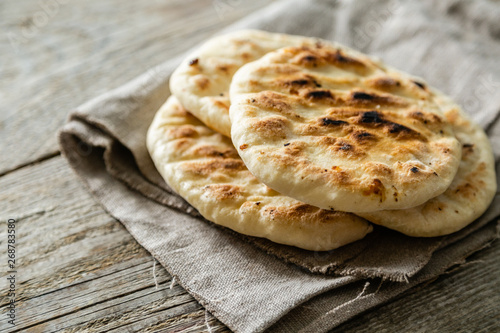 Traditional pita bread on rustic wood background, copy space