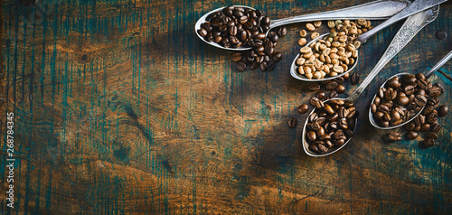 Assorted roasted and raw coffee beans in spoons