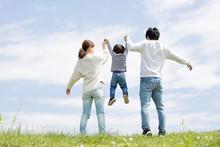 若い家族の全身後ろ姿、青空背景