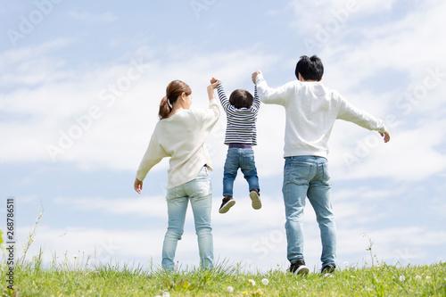 若い家族の全身後ろ姿、青空背景 Canvas Print