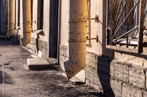 Valokuva  Old yellow drainpipes on a building wall in the morning sun