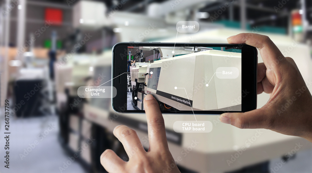 Fototapeta Augmented reality concept. AR. Industrial 4.0 , Hand of engineer holding mobile smart phone using virtual AR to check the work of electric machine on smart factory background.