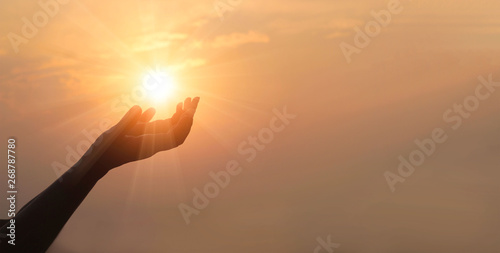 Canvas Print - Woman hands praying for blessing from god on sunset background