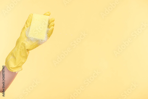 cropped view of cleaner in yellow rubber glove holding sponge with bubbles on yellow background