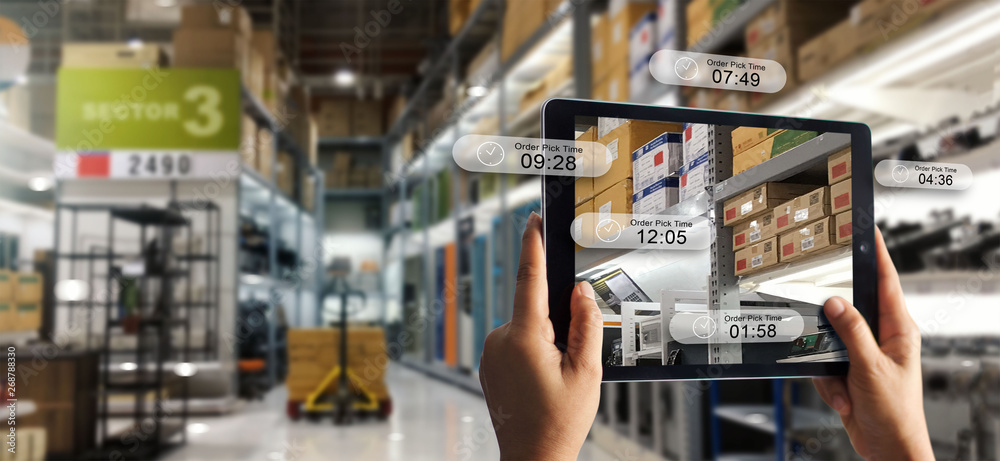 Fototapeta Augmented reality online shopping concept. E-commerce and digital marketing. Hand holding digital tablet smart phone use AR application to check order pick time on storage factory background.