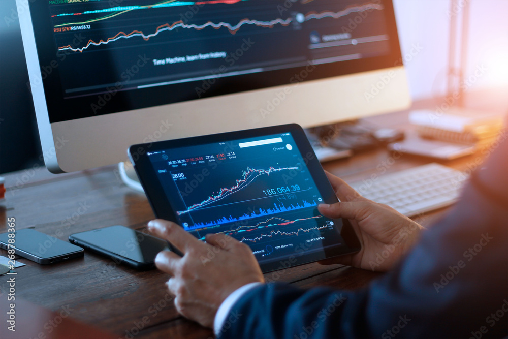 Fototapeta Businessman checking stock market on digital tablet and a desktop computer with stock exchange graph on screen. Financial stock market. Analyzing data in office background.