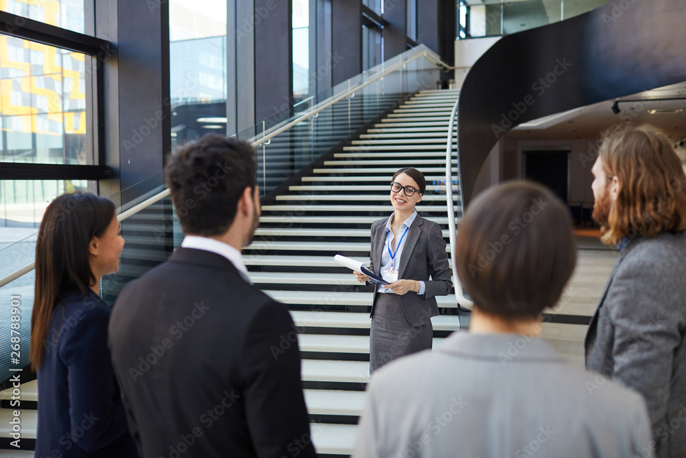 Fototapeta Smiling confident business forum guide with badge on neck standing on stairs and holding clipboards with files while giving tour to participants