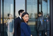 Content Beautiful Young Black Woman In Dark Blue Jacket Looking At Camera While Coming In Office Building Through Revolving Door