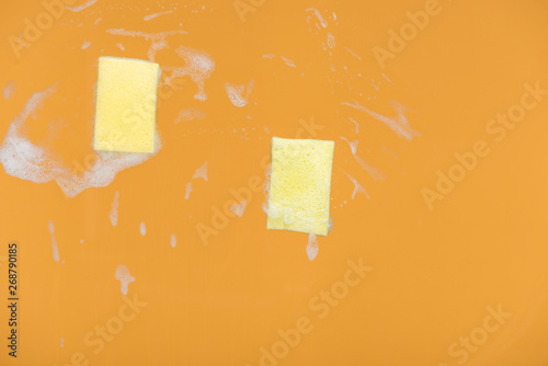 yellow sponges with foam on orange background