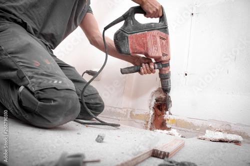 Foto Installateur stemmt Loch mit Hilti Bohrhammer in die Wand auf der Baustelle