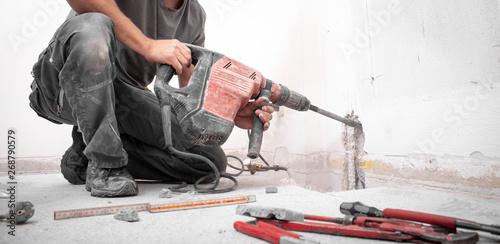 Cuadros en Lienzo  Installateur stemmt Loch mit Hilti Bohrhammer in die Wand auf der Baustelle