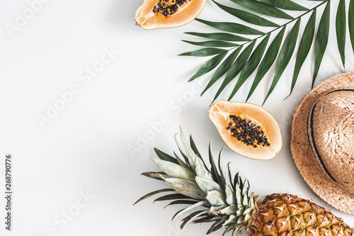 Summer composition. Tropical palm leaves, hat, papaya, pineapple on pastel gray background. Summer concept. Flat lay, top view, copy space