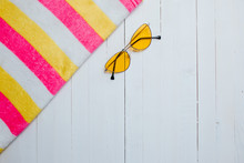 Yellow Sunglasses And Striped Colorful Towel On The White Wooden Bakground.