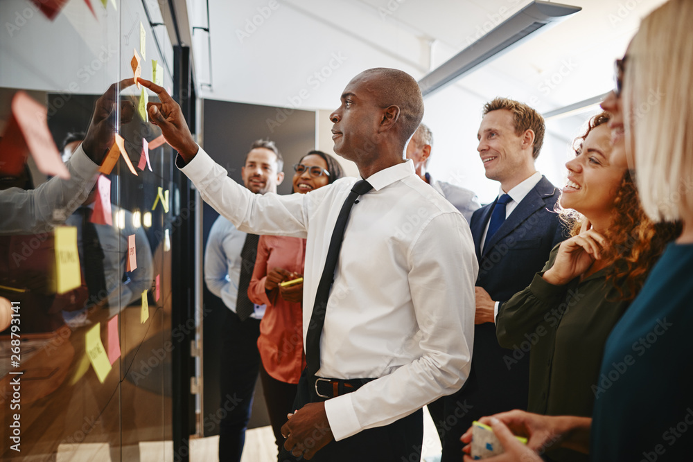 Young African businessman and his team brainstorming with sticky