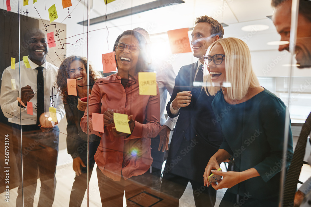 Fototapety, obrazy: Laughing businesspeople having a brainstorming session in an off