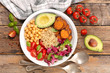 buddha bowl with avocado, chickpea, tomato and sweet potato