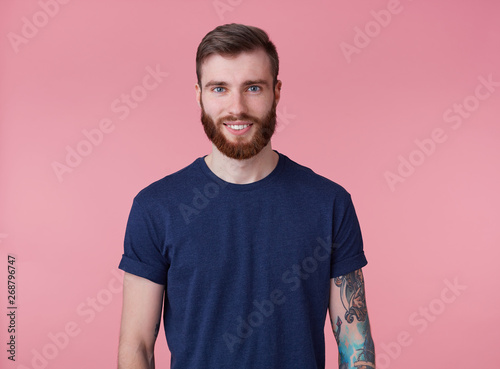 Carta da parati  Portrait of young happy attractive red-bearded guy with blue eyes, wearing a blue t-shirt, smiling and looking at the camera isolated over pink background