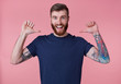 canvas print picture - Portrait of young happy attractive red-bearded young guy , wearing a blue t-shirt, broadly smiling, enjoy himself, with arms raised up and pointing fingers at himself isolated over pink background.