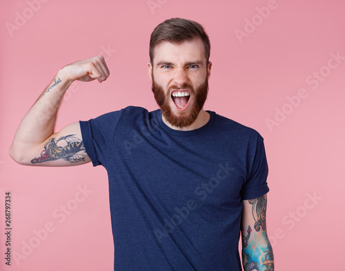 Photo Young screaming red-bearded handsome manful guy demonstrates biceps and strength, looking at the camera isolated over pink background