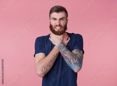 Fotografie, Obraz  Young red-bearded frowning guy, can't find a way out, displeased and angry, trying to strangle himself, scowl and grin isolated over pink background
