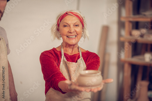 Happy aged woman showing you a clay pot