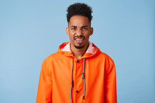 Dissatisfied Young African American Dark Skinned Guy Wears In Orange Rain Coat, Feels Very Upset, Frowns And Looks With Disgust At The Camera, Stands Over Blue Background.