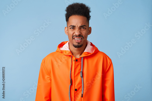 Dissatisfied young african american dark skinned guy wears in orange rain coat, feels very upset, frowns and looks with disgust at the camera, stands over blue background Tablou Canvas