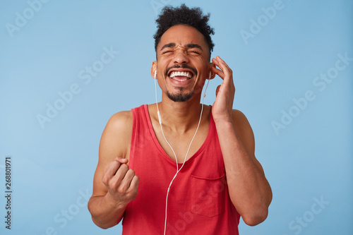 Photo of young dark skinned man feels great and very happy, close eyes, clenches his fist and enjoys his favorite song, sings along stands over blue background. - 268801971