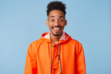 Close Up Of Happy Amazed Young African American Dark Skinned Man, Feels Great, Wears In Orange Rain Coat, Broadly Smiles Isolated Over Blue Background.