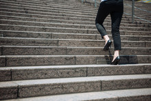 Legs And Feet Detail Of Businesswoman Climbing Stairs Outdoors In Urban Area. Unrecognized Office Lady Going To Work Wearing High Heels Walking In Company Building In Busy City In Morning Sunny Day