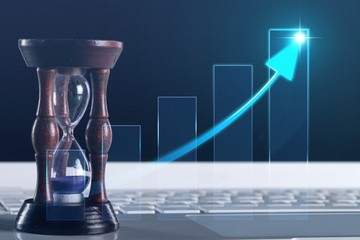 Sand running through the bulbs of an hourglass on business chart background