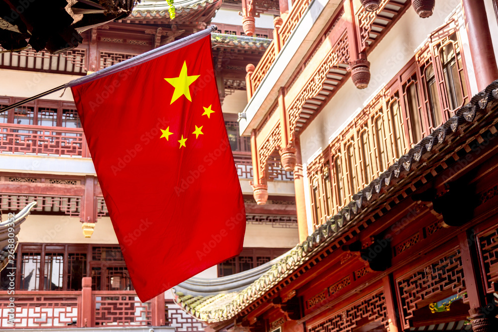 Red national flag of China against old chinese buildings at Yuyuan Garden in Shanghai, China.