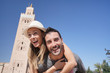 canvas print picture - Portrait of man giving piggyback ride to girlfriend in Koutoubia gardens