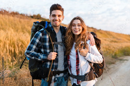 Cheerful young couple carrying backpacks hiking together Tableau sur Toile