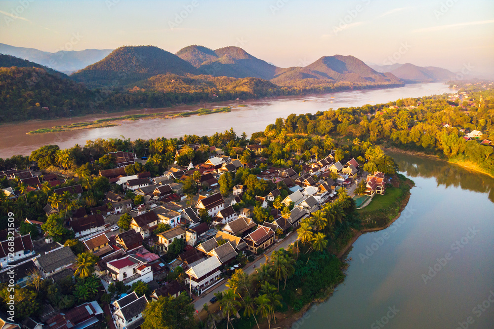 Fototapety, obrazy: Aerial view of Luang Prabang and surrounding lush mountains of Laos. Nam Kahn River, a tributary of the Mekong River, flows peacefully on the right.