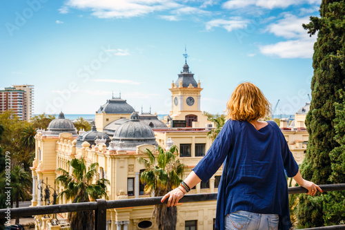 Foto woman with blue shirt enjoys the view over the town of Malaga, Spain