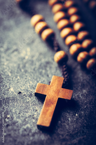 Foto Cross and rosary on stone background.