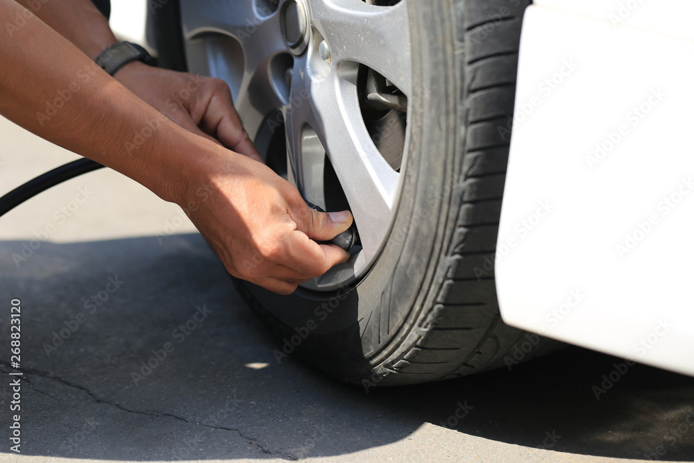 Fototapety, obrazy: Close-up of car mechanic working and pumping air into auto wheel in auto repair service.