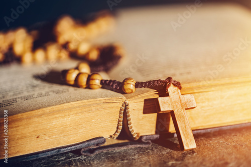 Fotografía Rosary with cross laying on a Bible book.