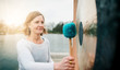 canvas print picture - Portrait einer glückliche Frau, die einen großen Gong zur Meditation am See schlägt