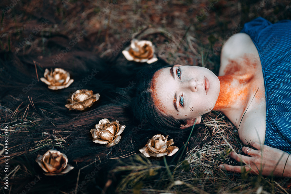 Fototapety, obrazy: portrait of beautiful brown-haired woman in a blue dress lying on grass, with golden roses on her long hair, in the fairy forest, golden paint shimmer on her neck fantasy concept