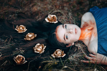 Portrait Of Beautiful Brown-haired Woman In A Blue Dress Lying On Grass, With Golden Roses On Her Long Hair, In The Fairy Forest, Golden Paint Shimmer On Her Neck Fantasy Concept